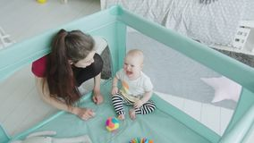 Cute baby girl crying sitting in playpen at home stock video footage