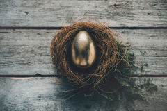 Close-up top view of golden Easter egg in nest on wooden table. Happy Easter concept Royalty Free Stock Photo