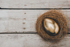 Close-up top view of golden Easter egg in nest on wooden table. Happy Easter concept Stock Photos
