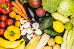 Close-up top view image of fresh organic vegetables and fruit. L. Ocally grown bell pepper, corn, carrot, mushrooms and other natural vegan food laying on black stock photography