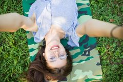 Close up top view of laughing brunette woman in eyeglasses lying on grass in park and making selfie stock image