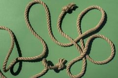 Close-up top view of nautical rope with knots and shadow. On green royalty free stock image