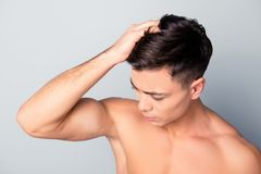 Close up top view photo of clean clear smooth, health fresh hair. Confident handsome man is fixing his furfur, isolated on grey background royalty free stock image