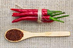 Close-up top view of red chili pepper, tied with braid and spoon on cloth with sackcloth stock photo