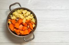 Close up, top view. Soup pot with sliced ingredients for pumpkin cream soup: carrot, pumkin, onion, potatoes. Plant-based food on the white wooden background royalty free stock image