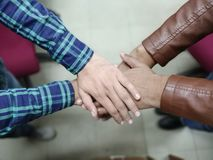 Close up top view of young business people putting their hands together. Stack of hands. Unity and teamwork concept stock photography