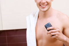 Close up of topless man holding electric razor Stock Photos