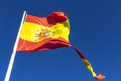 Torn Spanish flag waving on the wind Royalty Free Stock Photos