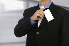 Close up torso businessman in formal suit. Taking smartphone from his pocket Stock Image