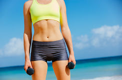 Close-up of torso of fitness woman barbells Royalty Free Stock Image