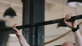 Close-up tough muscular young European man easily doing chin-up exercises during workout in large gym slow motion.