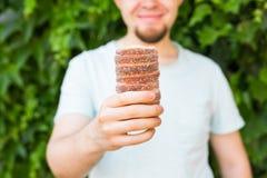 Close-up of tourist holds in hand Trdlo or Trdelnik background. Fresh Appetizing Trdlo or Trdelnik - Traditional Stock Photo