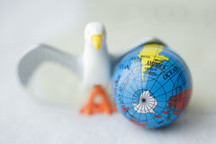 Close up of toy bird next to earth globe against white b Royalty Free Stock Photo