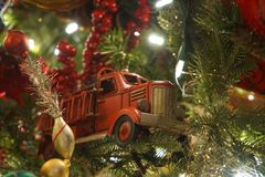 Firetruck Ornament. Close up of Toy Firetruck Ornament in Decorated Christmas Tree Stock Photos
