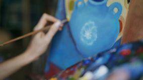 Close up tracking shot of woman`s hand mix paints with brush in palette and painting still life picture on canvas in. Close up tracking shot of female hand mix stock footage