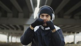 Close-up tracking shot of sportive man boxer in headphones doing boxing exercise in urban location outdoors in winter stock footage