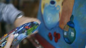 Close up tracking shot of woman`s hand mix paints with brush in palette and painting still life picture on canvas in. Close up tracking shot of female hand mix stock video