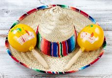 Close up of traditional Cinco De Mayo objects on white weathered. Close up view of traditional maracas and a large sombrero for Cinco de Mayo holiday celebration Royalty Free Stock Photo