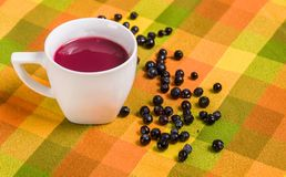 Close up of traditional Ecuadorian dish, colada morada with some mortinos, over a colorful fabric Royalty Free Stock Images