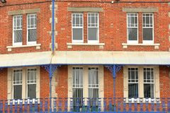 Close-up on traditional facades with brickstone and wrought iron railing balconies in Swanage Royalty Free Stock Photo