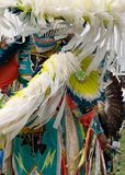 Close Up of the Traditional Garments Worn by a Fancy Dancer at a Pow Wow. Close up of the feathered headdress, arm shields and traditional fringed garment worn royalty free stock image