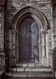 Close-up of traditional gothic medieval wooden entrance doorway with ancient brick arc, mystical portal stock photo