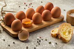 Close up. Traditional ingredients for breakfast. Fresh farm eggs in a wooden tray, next to chunks of baguette with cheese
