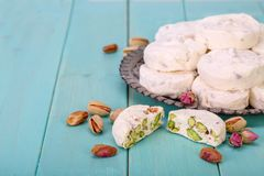 Close up of Traditional Iranian and Persian pieces of white noug. At dessert sweet candies Gaz with Pistachio nuts from Isfahan City on blue turquoise wood Stock Photo