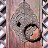 Close-up of a traditional Korean door handle. Close-up view of the design of a traditional korean door latch/handle on wooden doors with a lattice design Stock Images