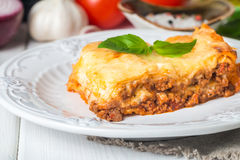 Close-up of a traditional lasagna. Made with minced beef bolognese sauce topped with basil  leafs served on a white plate Stock Photography