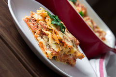 Close-up of a traditional lasagna topped with parskey leafs served on a white plate Stock Image