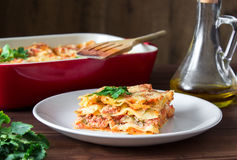 Close-up of a traditional lasagna topped with parskey leafs served on a white plate Stock Photography