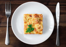 Close-up of a traditional lasagna topped with parskey leafs served on a white plate Royalty Free Stock Photo