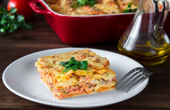 Close-up of a traditional lasagna topped with parskey leafs served on a white plate with fork Stock Photo