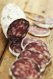 Traditional sliced meat sausage salami on wooden board Stock Image