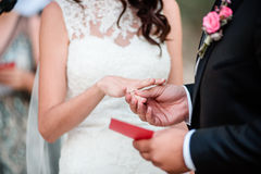 Close-up at traditional wedding ceremony outdoors. Groom is wearing a wedding ring at a wedding outdoors ceremony Royalty Free Stock Photography