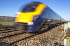 Close up of train speeding through English countryside on bright Stock Photo