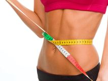 Close up of trained belly with measuring tape Royalty Free Stock Photography