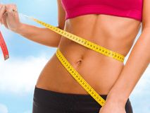 Close up of trained belly with measuring tape Royalty Free Stock Image