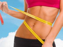 Close up of trained belly with measuring tape Stock Images