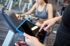 Close up of trainer hands with tablet pc in gym royalty free stock photos