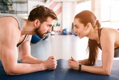 Close up of trainer and his student doing plank exercise together at the same time. They are concentrated on workout and. Looking at each other. Cut view Royalty Free Stock Photos