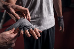 Close up trainer wrapping hand of trainee Stock Photography