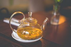 Close-up transparent glass teapot with sea buckthorn tea on the table stock photo