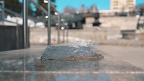 Piece of ice melts under hot sunbeams. Close-up of transparent ice melts on a gray pink marble barrier under the bright sun on a warm spring day against a stock video footage