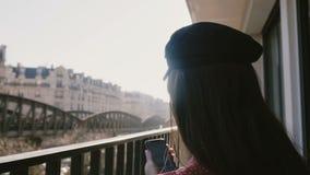 Close-up traseiro do alargamento da lente de vista, mulher elegante bonita feliz que usa o smartphone no balcão ensolarado idílic filme