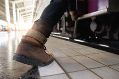 Close up of traveler feet step up to a passing train Stock Images