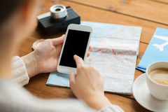 Close up of traveler hands with smartphone and map Stock Image