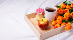 Close up of tray with cup of tea, jar of jam or honey, apple and Royalty Free Stock Photography