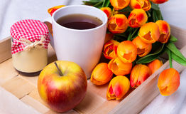 Close up of tray with cup of tea, jar of jam or honey, apple and Stock Image
